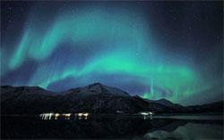 Sjøen speiler både nordlyset og lysene på land. (Foto: Frank Olsen)
