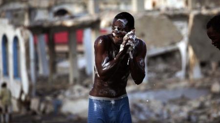 Enormt mye opprydnings- og gjenoppbyggingsarbeid gjenstår fortsatt på Haiti etter jordskjelvkatastrofen i januar. Mange må vaske seg i skittent kloakkvann, som denne gutten. (Foto: AP)