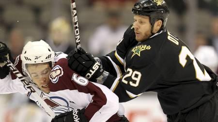 TØFFE TAK: Jonas Holøs kan forvente seg tøffe tak i NHL. Her får han en smell i en duell med Steve Ott i en treningskamp mot Dallas Stars. (Foto: RONALD MARTINEZ/Afp)