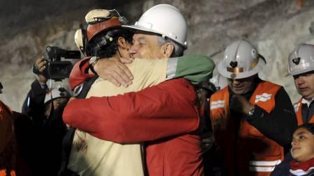 PRESIDENTKLEM: Den første gruvearbeideren blir møtt av Chiles president Sebastian Pinera og en klem. (Foto: Jose Manuel de la Maza/Ap)