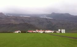 Denne gården ligger like sør for Eyjafjallajökul, rett under breen. Den hvite kanten oppe i fjellet er iskanten. Det mørke området over er også is, fortsatt dekket av aske.  (Foto: Ronald Toppe)