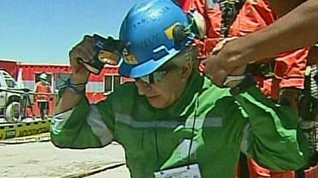 GIKK NED PÅ KNE: Vel oppe i dagslyset gikk gruveveteranen og   bestefar Omar Reygadas ned på kne med bibelen i hånda. (Foto: APTN)