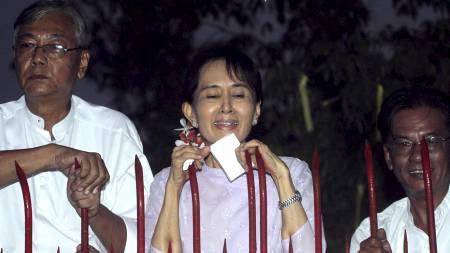 HYLLES: Aung San Suu Kyi mottar blomster fra tilhengere utenfor   sitt hjem etter løslatelsen fra husarrest. (Foto: Khin Maung Win/Ap)
