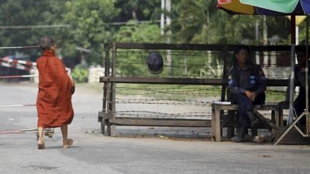 HUSARREST: En munk ved porten til Aung San Suu Kyis hus. En   soldat sitter vakt ved porten. (Foto: Soe Zeya Tun/Reuters)