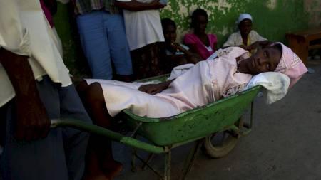 Den månedslange kolera-epidemien har så langt tatt livet av minst 1000 mennesker på Haiti. Denne kvinnen har symptomene, og måtte onsdag fraktes til sykehus i trillebår. (Foto: Ramon Espinosa/Ap)