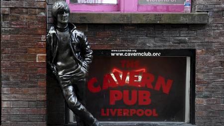 HYLLES: En statue av en ung John Lennon utenfor legendariske Cavern Pub i Liverpool. Det vil bli holdt et fakkeltog i byen onsdag for å markere Lennons dødsdag. (Foto: PAUL ELLIS/Afp)