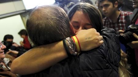 GJENFORENT: Slektninger omfavner hverandre på flyplassen i Madrid etter sikker utflukt fra Tripoli. (Foto: JUAN MEDINA/Reuters)