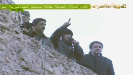 TALTE TIL TILHENGERE: - Vi er klar for å vinne over fienden. Vi vil slåss, og vi vil slå dem, sa Muammar al-Gaddafi i en tale på Den grønne plass i Tripoli fredag kveld.  (Foto: statlig tv)