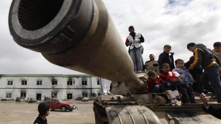 TOK KONTROLL: En gruppe barn har okkupert denne ødelagte tanksen på militærbasen Al-Katiba i byen Benghazi etter at demonstranter og soldater tok kontrollen av byen. (Foto: SCANPIX)