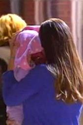 TILBAKE HOS I MORS ARMER: Den lille jenta blir båret ut av sin   mor. (Foto: CBS)