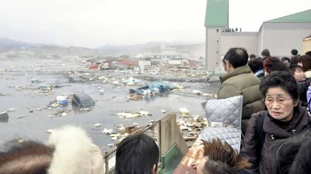 OVERSVØMMES: Innbyggerne i Kesennuma har måttet trekke opp på hustak for å komme seg unna vannmassene. (Foto: YOMIURI/Reuters)