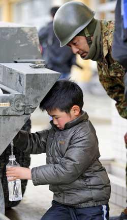 En gutt fyller vann på flaske i en av leirene i byen Rikuzentakata   mens en soldat følger med. (Foto: Kazuhiro Nogi/Afp)