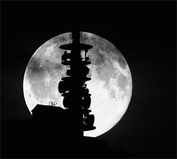 Fullmånen stiger opp bak masten på Ulriken i Bergen i desember 2008. (Foto: Pål Bentdal)