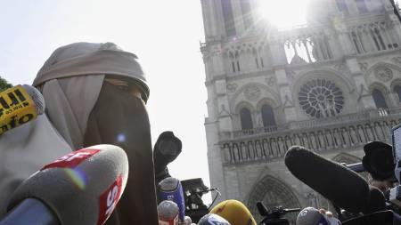 DEMONSTRERTE: En kvinne kledt i niqab holder en apell utenfor Notre-Dame-katedralen i Paris mandag. To kvinner som deltok i demonstrasjonen ble pågrepet av politiet. (Foto: BERTRAND GUAY/Afp)
