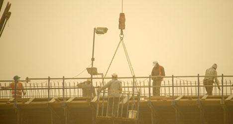 Arbeidere på en bro i Kuwait må bruke støvmasker. (Foto: Reuters)
