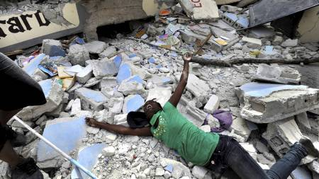 This handout photograph by Carol Guzy of the Washington Post won the 2011 Pulitzer Prize for Breaking News Photography as announced in New York April 18, 2011. Cindy Tersme throws herself amid the rubble of Ecole St. Gerard, Haiti, screaming in anguish as she searches for her brother Jean Gaelle Dersmorne, 14.