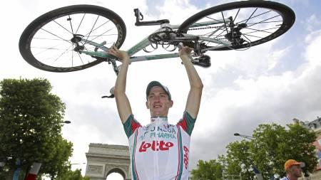 Jurgen van den Broeck løfter sykkelen i glede over å ha fullført   Tour de France 2010. (Foto: Bas Czerwinski/Ap)