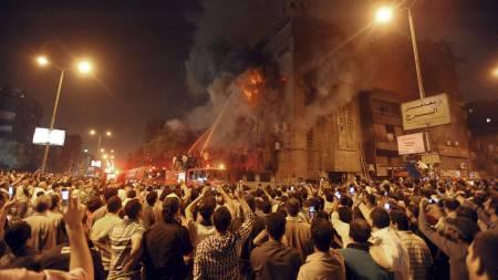 FLAMMENDE RASERI: Brannvesenet kjemper mot flammende etter at muslimer satte fyr på en kirke i Kairo sent lørdag kveld. (Foto: AP/Ap)