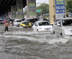 Bilistene forsøker å komme seg over en oversvømt vei vest for Manilla. (Foto: Ap)