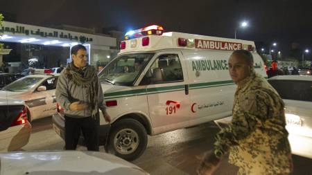 LUFTANGREP FRA NATO: En libysk soldat og sivile prøver å dirigere trafikken tilbake til normalen etter luftangrepet natt til tirsdag (Foto: Darko Bandic/Ap)