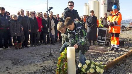 Daniel Nordmo, Sander Bjerknes og Leif Nordmo la ned en krans på vegne av de pårørende under markeringen av ettårsdagen for togulykken på Sjursøya som kostet tre mennesker livet. (Foto: Terje Bendiksby)