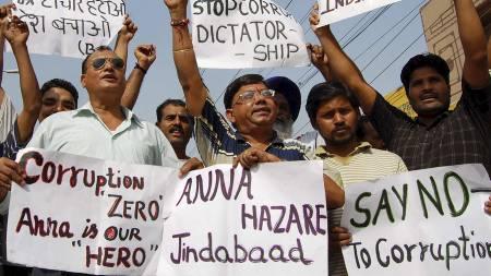 PROTESTER: Tilhengere av den indiske aktivisten Anna Hazare holder plakater med salgord mot indias statsminister  Manmohan Singh. (Foto: NARINDER NANU/Afp)