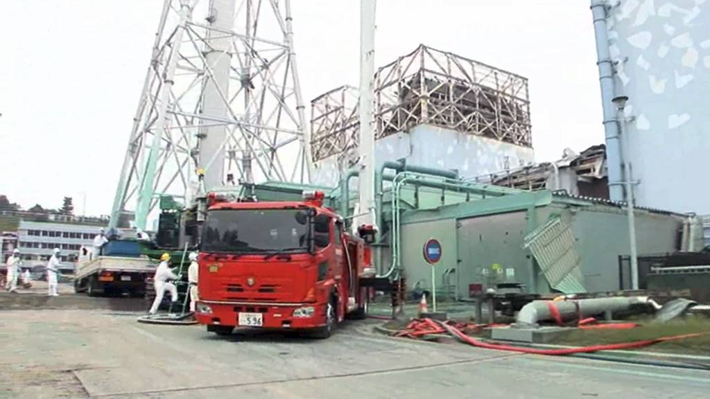 STORE UTSLIPP: Arbeidere sprayer et stoff som skal hindre støv fra å slippe ut fra det ødelagte atomkraftverket i Fukushima 1. juni. (Foto: HO/Afp)