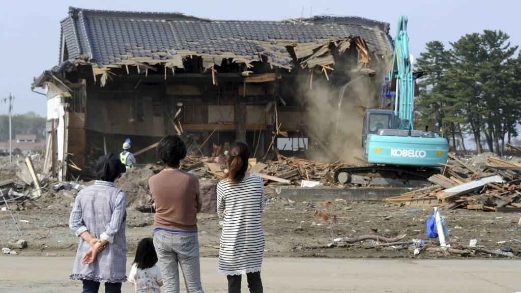 MANGE RAMMET: Klimaendringer og naturkatastrofer sender millioner av mennesker på flukt. Her ser en japansk familie på at huset deres jevnes med jorden i den tsunami-rammede byen Natori. (Foto: TOSHIFUMI KITAMURA/Afp)