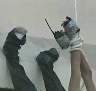 SLIK GJØR DE DET: Med hendene surret sammen med teip og festet med kraftig tau, ble de tre mennene kastet ut fra en bro over en av Monterreys mest trafikkerte veistrekninger. (Foto: APTN)