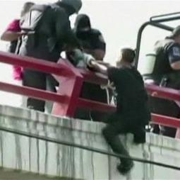 ENDELIG REDDET: Politimenn hjelper til slutt tenåringen over rekkverket, på broen over motorveien. (Foto: TV Azteca)