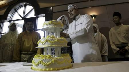 I forbindelse med åpningen av «Lydig kone-klubben», ble nygifte invitert på fest. Her er et ungt par i ferd med å sette spaden i bryllupskaken. (Foto: AP/Ap)