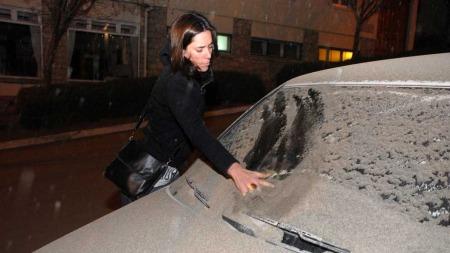 ASKESKY: En kvinne i San Carlos de Bariloche, sør i Chile fjerner aske fra vindusruten på bilen sin. (Foto: Sanpix / Alfredo Leiva )