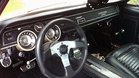 Det er ikke vanskelig å se slektskapet til Mustangen når man ser interiøret i Mercury Cougar. Moderne ratt, klassiske terninger i speilet og gulvmatte med dødninghode på gir den rette stemningen. Foto: Privat