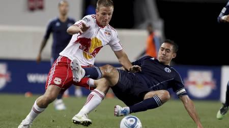 UNDER KAMP: Her blir Davy Arnaud i det amerikanske laget Sporting   KC taklet av Jan Gunnar Solli. (Foto: Scanpix/Afp)