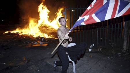 En nasjonalist vaier med det britiske flagget i forbindelse med at protestanter feirer at William of Orange beseiret katolske James II i 1690. (Foto: Colm O'Reilly/Ap)