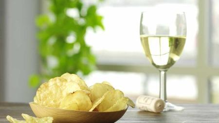 Et glass hvitvin med 12 prosent alkoholinnhold inneholder ca.   80 kcal. Blir du fristet til ta en håndfull potetgull kan du plusse på   153 kaloier. (Foto: Illustrasjonsfoto)