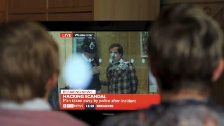 PÅGREPET: Her står politiet med det som skal være komikeren Jonnie Marble, som stod bak angrepet. (Foto: ANDREW YATES/Afp)