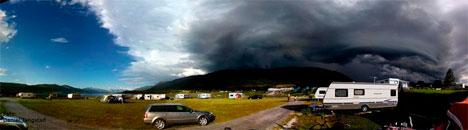 Panoramabildet av tordenskyen viser hvor brått blå himmel kan gå over til lyn og regn. (Foto: Daniel Tangstad)
