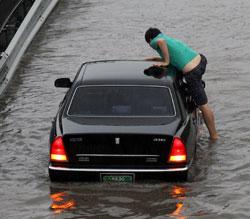 En mann klatrer opp på taket på bilen sin for å komme seg bort fra vannmassene. (Foto: Reuters)