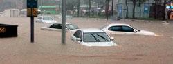 Flere biler står delvis under vann i på en oversvømt vei i Seoul. (Foto: Reuters)