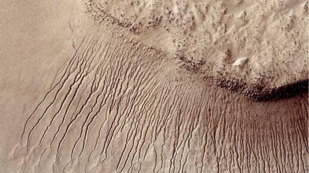 Dette bildet fra en av NASAs romsonder viser et svært detaljert bilde av Mars' overflate. Her er flere kanaler, fra én til ti meter brede i et krater. Enkelte forskere mener disse beviser at det finnes flytende saltvann på den røde planeten. (Foto: HO/Afp)