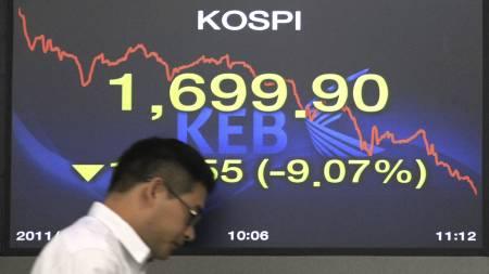 NEDGANGEN FORTSETTER: En valutahandler passerer en skjerm som viser utviklingen på Kospi-indeksen i Seoul 9. august. (Foto: Ahn Young-joon/Ap)