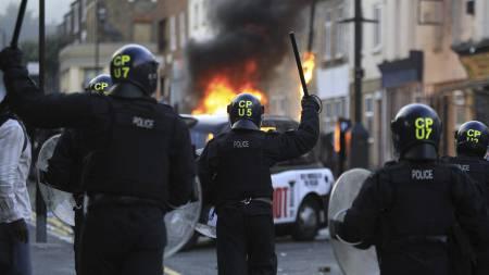 GATEKAMPER: Opprørspoliti settes inn mot pøbler i Hackney etter at butikker og biler ble påtent mandag. (Foto: Lefteris Pitarakis/Ap)