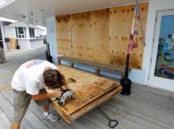 Jeremy Pickett skrur plater forran vindeuene i butikken sin på Cape Hattereas i North Carolina. (Foto: AP Photo/Jose Luis Magana)