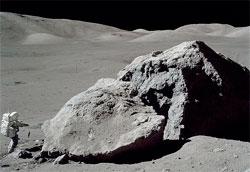 Schmitt tar prøver av en stor stein som er delt i to. (Foto:   NASA)