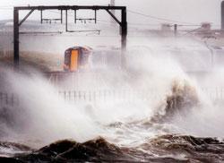 I Storbritannia er flere togavganger  innstilt på grunn av trær på linjen. Dette toget tøffer gjennom spruten fra store bølger ved Saltcoats i Skottland. (Foto: AP Photo/PA, Danny Lawson)