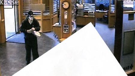 TRUER MED VÅPEN: Bildet viser raneren inni banken mens han truer   en ansatt med et våpen. (Foto: Overvåkningskamera, Sparebanken Pluss,   Vigeland)