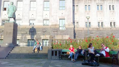 Folk koser seg i solen utenfor teateret i Bergen torsdag. (Foto: Ronald Toppe)