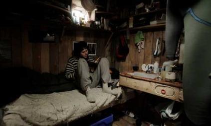 Inge har hengt fra seg våtdrakta og sitter inne i den lille hytta.  (Foto: Jørn N. Ranum, Inge Wegge )