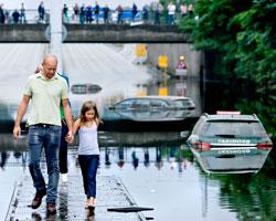 Far og datter går på midtdeleren på en oversvømt motorvei i København 15. august 2010. (Foto: Afp)